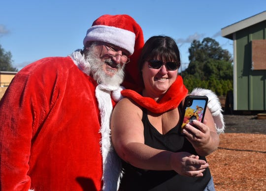 Santa poses for a picture with Debbie Marostica at Hagle Tree Farm in Somis.