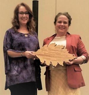 Diane Amico (left), chairperson, Vineland Environmental Commission, accepts the 2019 Green Communities Achievement Award on behalf of the commission from Carrie Sargeant, coordinator for the New Jersey Department of Environmental Protection State Forest Service's Urban and Community Forestry program.