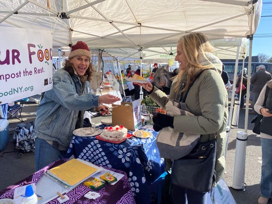 Volunteer Beth Radow (left) shares some cake with Pam Miner (right) at the Love Your Food kick-off at Larchmont Farmers Market.