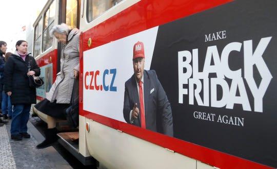 A woman gets off a tram advertising the Black Friday in Prague, Czech Republic, Thursday, Nov. 28, 2019. (AP Photo/Petr David Josek)