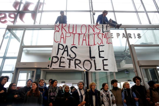 Activists block a shopping center, in the business district of Paris, La Défense, in Paris, Friday, Nov. 29, 2019. People don't celebrate Thanksgiving in France, or Denmark, or the Czech Republic, but they do shop on Black Friday. The U.S. sales phenomenon has spread to retailers across the Atlantic in recent years. The banner reads « Let's burn capitalism, not oil ».(AP Photo/Thibault Camus)