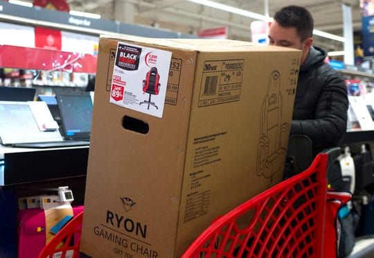 Shopper is seen during the opening of a Auchan general store, Friday, Nov 29, 2019 in Englos, northern France, during the Black Friday consumer sales event. Some French lawmakers want to ban Black Friday price reductions, the post-Thanksgiving sales event that has morphed into a global phenomenon. (AP Photo/Michel Spingler)