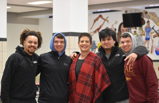Wichita Falls High School Principal Christy Nash, center, gathers with former Class of 2019 Coyote players at Thursday morning's practice. Alumni arrived to support the team before Friday's playoff game against Rider High School. Pictured with Nash, Will Beaver, Jacob Weaver, Anthony Vargas and Jerryd Weaver.