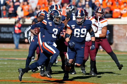 Virginia quarterback Bryce Perkins carries the ball against Virginia Tech during the first quarter at Scott Stadium.