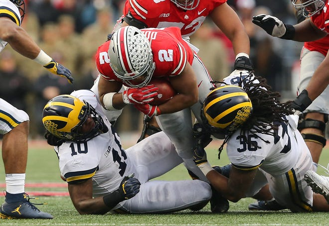 Ohio State running back J.K. Dobbins dives past two Michigan defenders during their game in 2018 at Ohio Stadium.