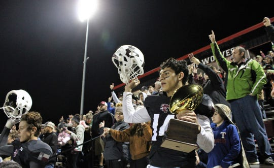 Junior quarterback Xavier Rodela raises his helmet while holding the trophy for winning a Class 2A DI third round game as Hawley fans celebrate a 22-21 win Friday over Sundown at Wolf Stadium in Colorado City.