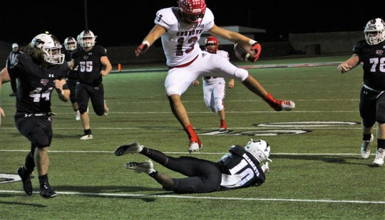 Sundown's Gavin Richardson (13) leaps over Hawley's Marcos Hernandez to gain yardage Friday in a Class 2A DI playoff game at Colorado City.