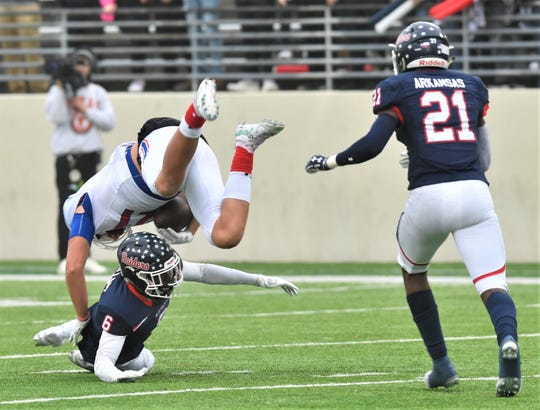 Denton Ryan's D.J. Allen (6) upends Cooper's Braiden Hill after a catch in the first half. Ryan beat the Cougars 58-20 in the Region I-5A Division I semifinal game Friday, Nov. 29, 2019, in Denton.