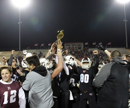 Hawley players and coaches raised the gold football high to celebrate Friday's 22-21 Class 2A DI playoff victory over Sundown at Colorado City.