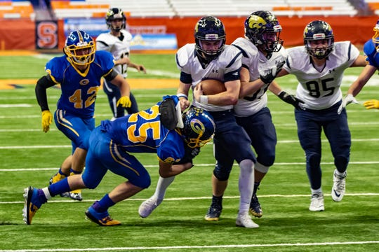 Game MVP Logan Haskell, a junior from Susquehanna Valley is being pulled down by Kyle Savage of Gouverneur at the Carrier Dome in Syracuse Friday night in the Class C State Football Championship.