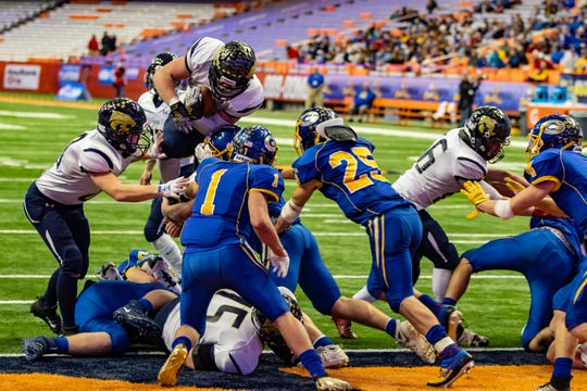 Susquehanna Valley Senior Mitchell Knapp leaps over a wall of Gouverneur defenders to score a touchdown on the way to a second straight Class C State Football Championship.