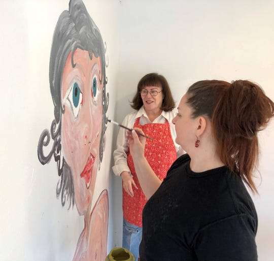 "Artist Jennifer Chamberlin paints inside Amy Burnett's former gallery space as Burnett looks on. ""The Paint People Project"" aims to cover the walls of Burnett's building before it sells in 2020."