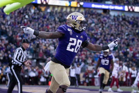 Washington running back Richard Newton celebrates after scoring a touchdown during the first half of an NCAA college football game against Washington State, on Friday, Nov. 29, 2019 in Seattle. (AP Photo/Stephen Brashear)