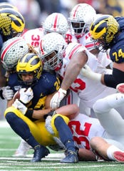 Michigan running back Zach Charbonnet is tackled by Ohio State defenders during the first half Saturday, Nov. 30, 2019, at Michigan Stadium.
