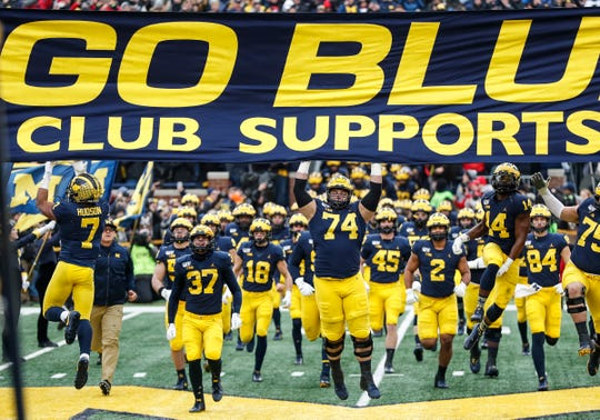 Michigan players jump up to touch the banner as they take the field for the Ohio State game at Michigan Stadium, Saturday, Nov. 30, 2019.