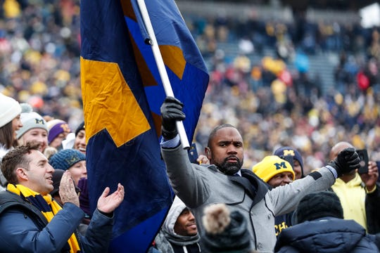 Charles Woodson waves a Michigan flag among fans before the Ohio State game at the Michigan Stadium in Ann Arbor, Saturday, Nov. 30, 2019.
