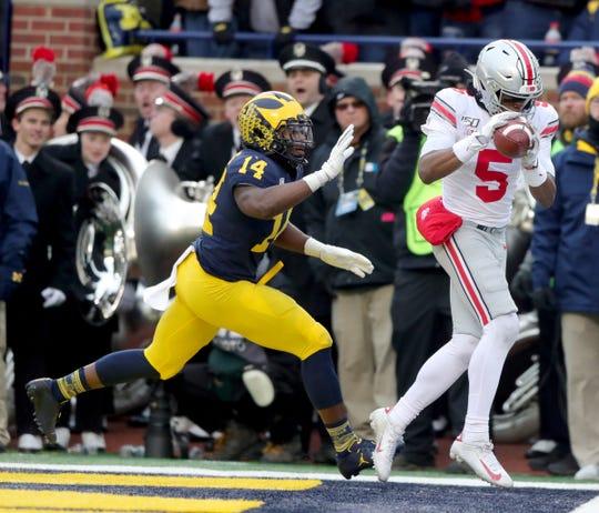 Ohio State Buckeyes receiver Garrett Wilson catches a touchdown pass over Michigan Wolverines safety Josh Metellus during the second half at Michigan Stadium in Ann Arbor, Saturday, Nov. 30, 2019.