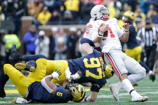 Ohio State quarterback Justin Fields is tackled by Michigan defensive lineman Aidan Hutchinson and  linebacker Josh Uche during the first half at the Michigan Stadium in Ann Arbor, Saturday, Nov. 30, 2019.