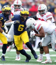 Michigan Wolverines linebacker Josh Uche tackles Ohio State Buckeyes running back J.K. Dobbins during the first half Saturday, Nov. 30, 2019 at Michigan Stadium.