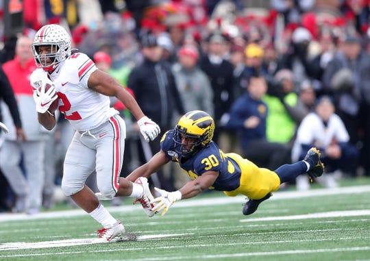 Michigan defensive back Daxton Hill trips up Ohio State running back J.K. Dobbins during the first half Saturday, Nov. 30, 2019, at Michigan Stadium.