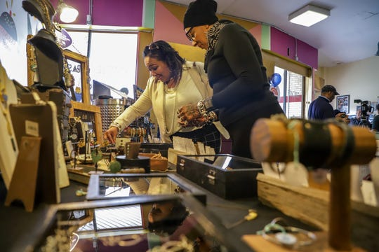 Bridget Tedford, left, of Redford Township looks over jewelry made by Stephanie Whitfield, of Salika's Handcrafted Jewels, during the Detroit Black Business Crawl at Good Cakes and Bakes vendor market on the Livernois Avenue of Fashion in Detroit on Small Business Saturday, Nov. 30, 2019.