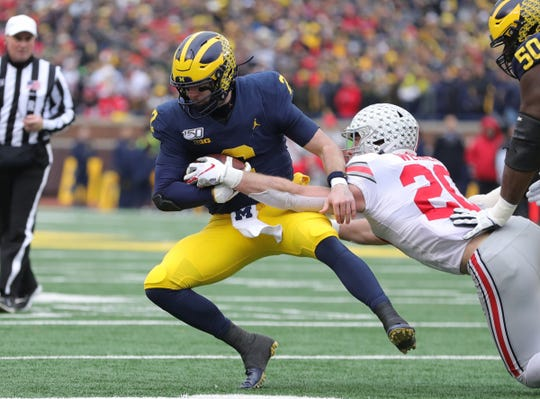 Michigan Wolverines quarterback Shea Patterson is tackled by Ohio State Buckeyes linebacker Pete Werner during the first half Saturday, Nov. 30, 2019 at Michigan Stadium.
