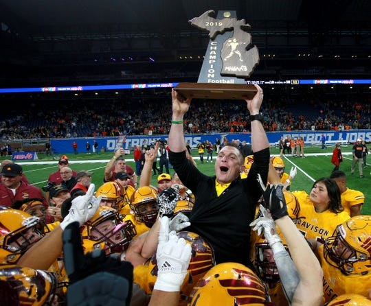 Davison head football coach Jake Weingartz celebrates the school's first ever state football championship on the shoulders of his football players after his team beat Brighton 35-25 in the Division 1 state championship football game at Ford Field on Saturday, November 30, 2019.