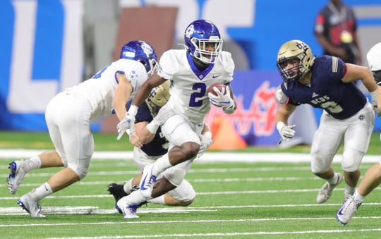 Grand Rapids Catholic Central's Malachi Love (2) runs by Detroit Country Day's Joe Miller (3) during the Division 4 title game Nov. 29, 2019, at Ford Field in Detroit.