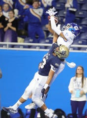 Grand Rapids Catholic Central's Jace Williams (5) catches a touchdown pass against Birmingham Detroit Country Day's Brandon Mann (13) during the Division 4 title game Nov. 29, 2019, at Ford Field in Detroit