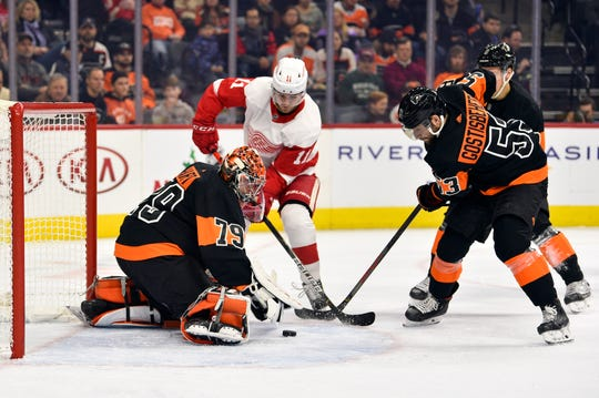 Philadelphia Flyers goaltender Carter Hart makes a save on a shot by Detroit Red Wings' Filip Zadina (11) as Shayne Gostisbehere defends during the first period Friday, Nov. 29, 2019, in Philadelphia. The Flyers won 6-1