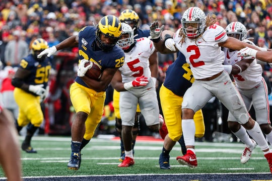 Michigan's Hassan Haskins runs past Ohio State's Chase Young (2) during the second half at Michigan Stadium, Saturday, Nov. 30, 2019.