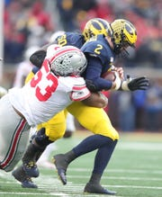 Michigan Wolverines quarterback Shea Patterson is sacked by Ohio State Buckeyes defensive tackle Davon Hamilton during the second half at Michigan Stadium in Ann Arbor, Saturday, Nov. 30, 2019.