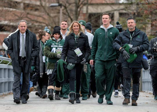 Michigan State quarterback Brian Lewerke walk over to Spartan Stadium with his parents on Senior Day prior to a game against Maryland on Saturday, Nov. 30, 2019.