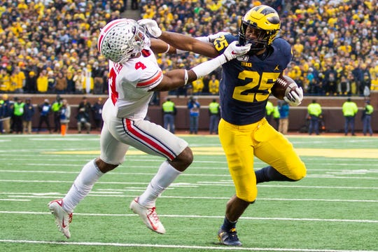 Ohio State safety Jordan Fuller grabs the facemask of Michigan running back Hassan Haskins at Michigan Stadium, Saturday, Nov. 30, 2019. Ohio State defeated Michigan, 56-27.