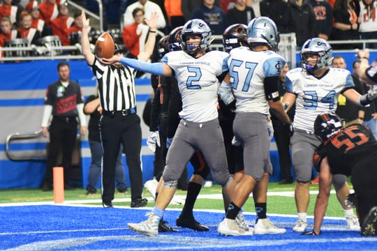 Lansing Catholic quarterback Zach Gillespie (2) reacts after running in for a touchdown against Almont in the first quarter.