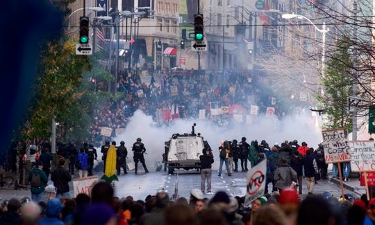 FILE - In this Nov. 30 1999, file photo, Seattle police use tear gas to push back World Trade Organization protesters in downtown Seattle.