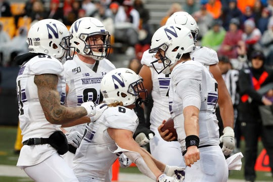 Northwestern quarterback Andrew Marty, right, celebrates his touchdown with teammates during the first half Saturday. Marty ran for 111 yards and two touchdowns while passing for another and Northwestern upset Illinois 29-10