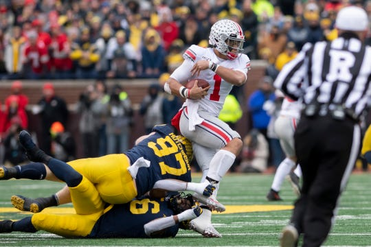 Ohio State quarterback Justin Fields is brought down by Michigan linebacker Josh Uche (6) and defensive lineman Aidan Hutchinson (97) in the second quarter.