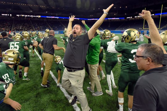 Monroe St. Mary Catholic Central head coach Adam Kipf, middle, celebrates with his team.
