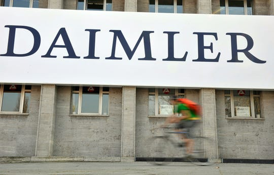 FILE - In this April 8, 2009 file photo, a cyclist passes a logo of German car company Daimler in Berlin.