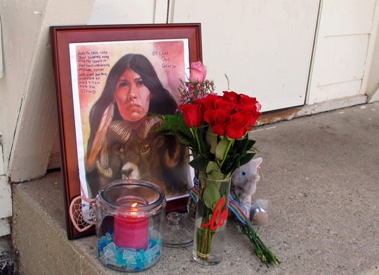 FILE - In a Monday, Aug. 28, 2017 file photo, a makeshift memorial to Savanna Greywind featuring a painting, flowers, candle and a stuffed animal is seen on Monday, Aug. 28, 2017, in Fargo, N.D., outside the apartment where Greywind lived with her parents.