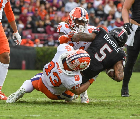 Clemson linebacker Chad Smith (43) tackles South Carolina running back Rico Dowdle(5) near Clemson safety Denzel Johnson(14) during the second quarter at Williams-Brice Stadium in Columbia, South Carolina Saturday, November 30, 2019.