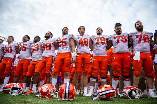 Clemson football players stand arm-in-arm singing their alma mater following their game at the Gamecocks' Williams-Brice Stadium in Columbia, Saturday, November 30, 2019.