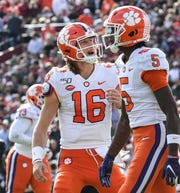 Clemson quarterback Trevor Lawrence (16) celebrates a touchdown by wide receiver Tee Higgins (5) during the first quarter at Williams-Brice Stadium in Columbia, South Carolina Saturday, November 30, 2019.