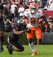 Clemson running back Travis Etienne (9) runs near South Carolina defensive end Aaron Sterling(15) during the first quarter at Williams-Brice Stadium in Columbia, South Carolina Saturday, November 30, 2019.
