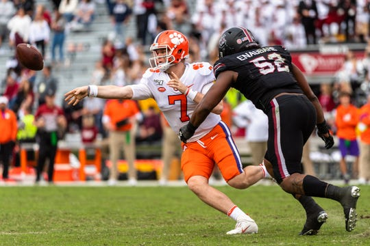 Clemson quarterback Chase Brice (7) passes the ball off before South Carolina defensive end Kingsley Enagbare(52) can get to him during their game at the Gamecocks' Williams-Brice Stadium in Columbia, Saturday, November 30, 2019.