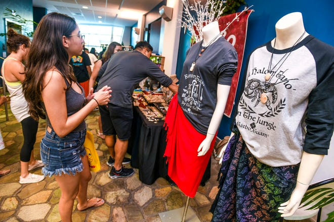 Gåtbo Guam owner Raymond Anderson interacts with a customer as another looks over displayed shirts during a holiday fair held at the Guam Museum in this Nov. 30, 2019, file photo.