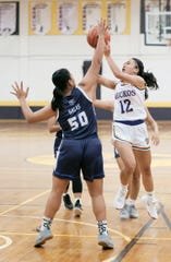 In this file photo from Nov. 29, George Washington Geckos (12) Haley Banez shoots through the defense of Notre Dame Lady Royals (50) Haley Salas during an IIAAG Girls Basketball game at the GW gym. The Guam Board of Education will revisit its May 2019 decision to separate high school sports at its regular board meeting scheduled for 6 p.m. Dec. 6 at Tiyan.