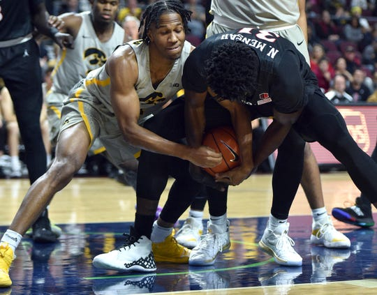 Iowa guard Bakari Evelyn (4) and San Diego State forward Nathan Mensah (31) fight for the ball during the first half of an NCAA college basketball game Friday in Las Vegas.