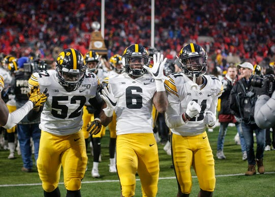 Iowa players (from left) Amani Jones, Ihmir Smith-Marsette and Michael Ojemudia celebrate Friday's 27-24 win against Nebraska.